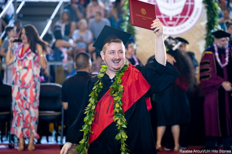 Male graduate in maile lei leaving dais.