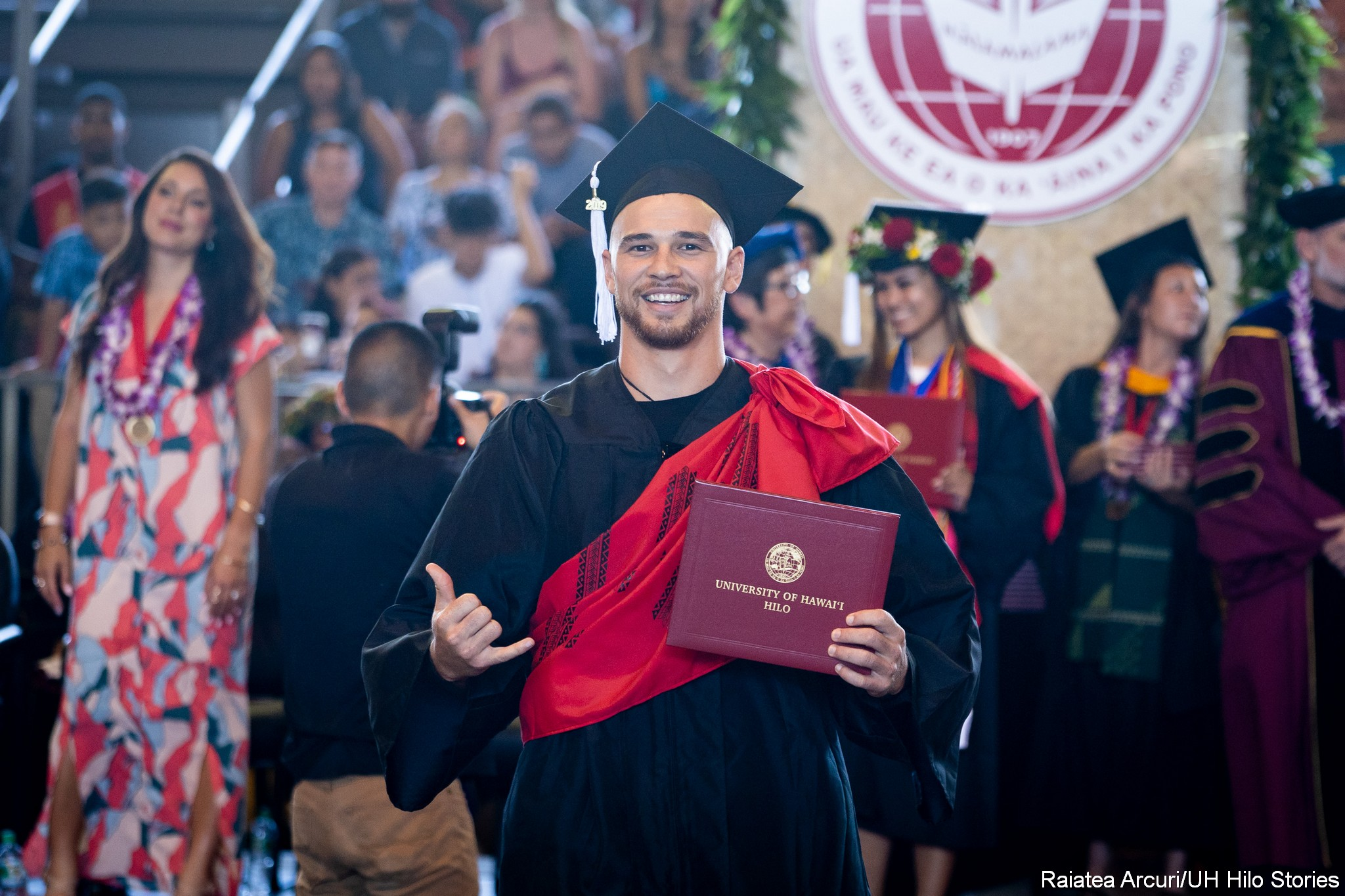 Male graduate leaving dais with diploma, flashing shaka with right hand.