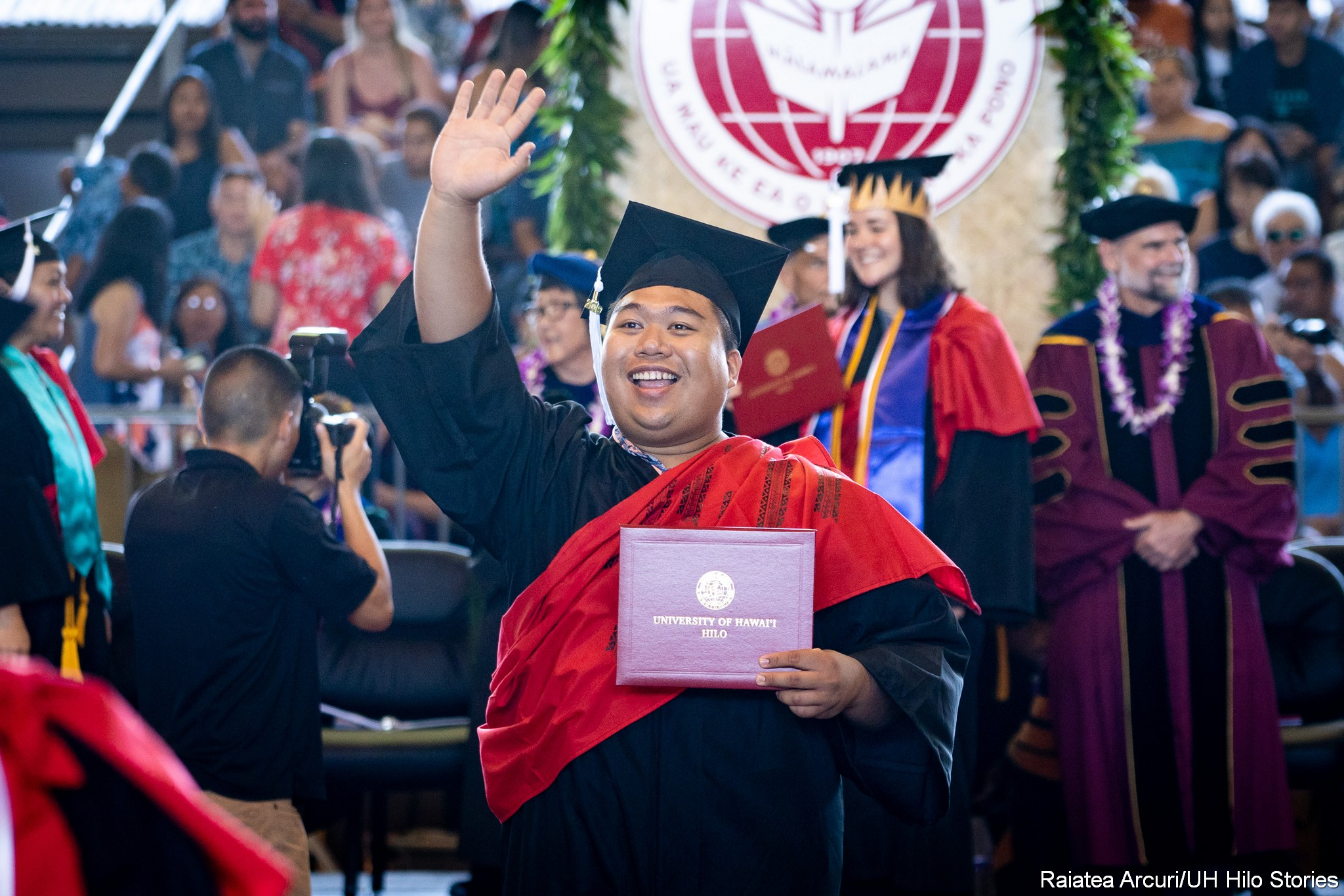 Graduate waves to audience while leaving dais with diploma.