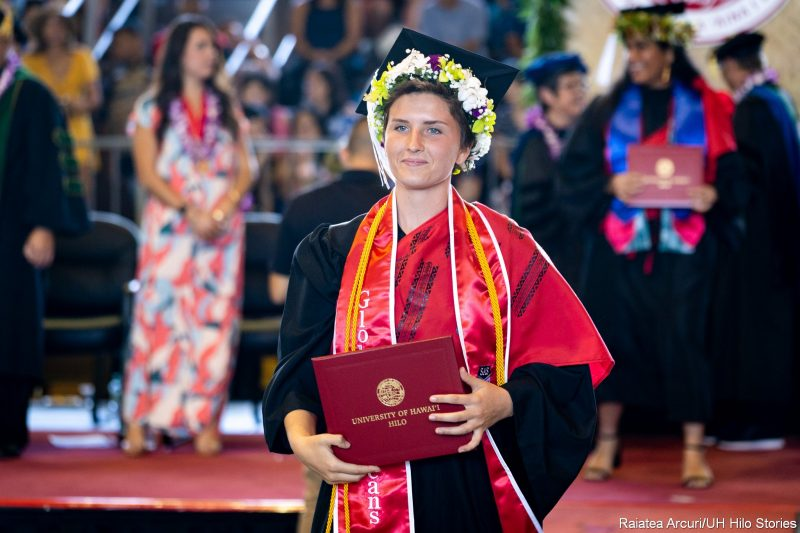 Subdued female graduate with wide red sash, gold cord, leaving dais with diploma.