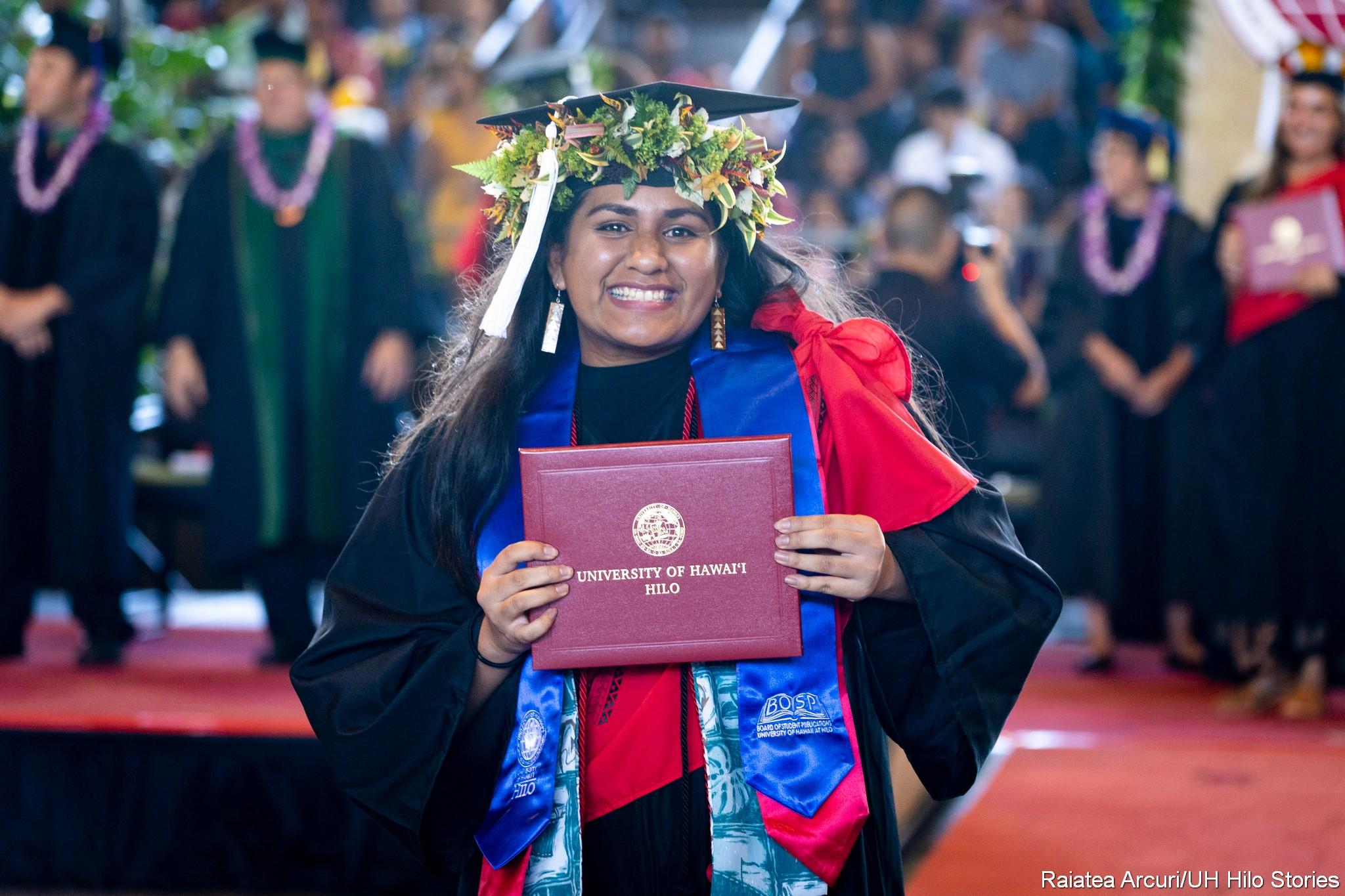 Graduate leaving dais with diploma.