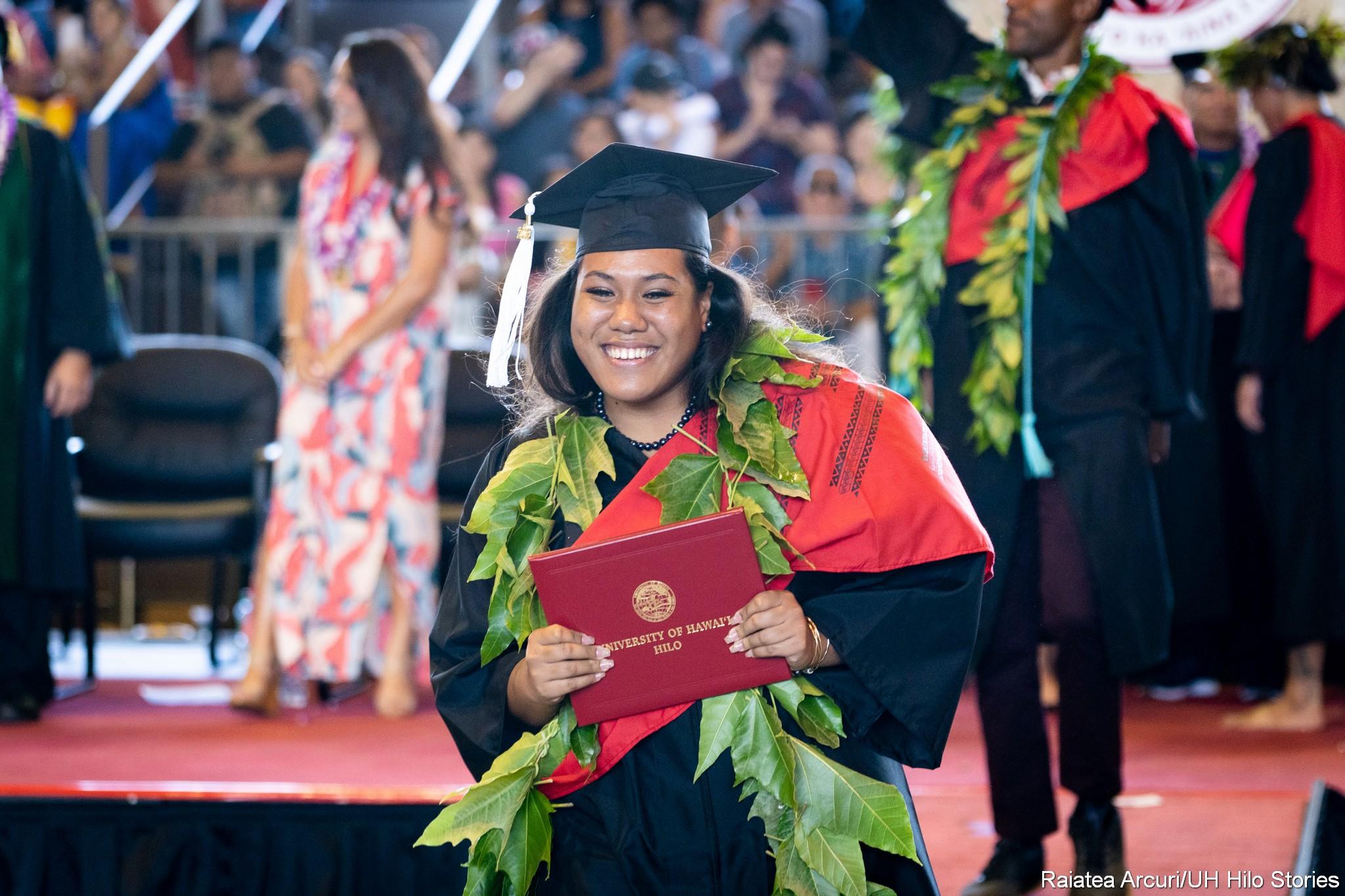 Big smile on female graduate leaving dais with diploma.