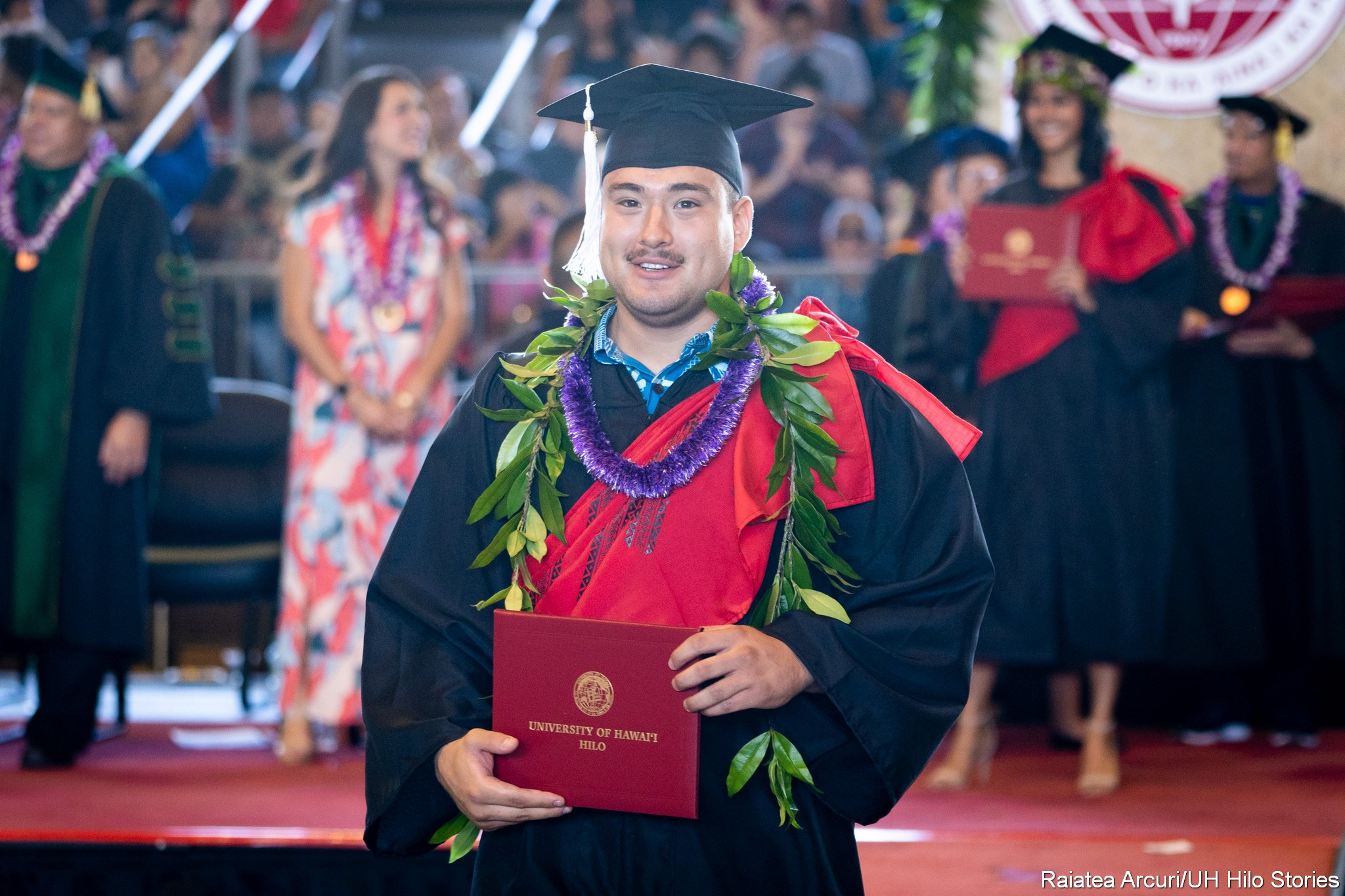 Male graduate with maile and purple lei leaving dais with diploma.