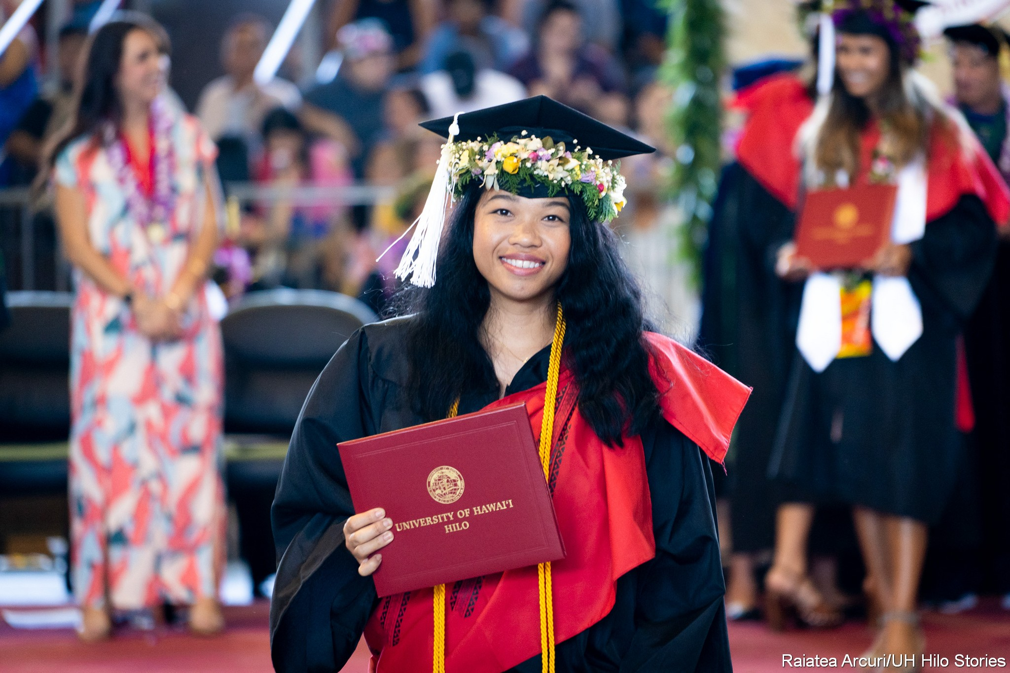 Female graduate with white head lei on cap and gold cord leaving dais with diploma, pauses for photo.