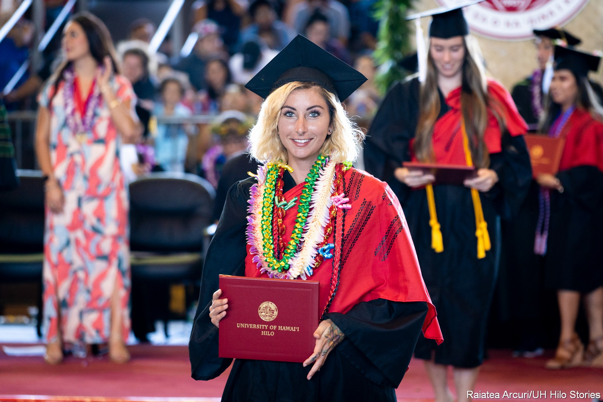 Female graduate with green, white lei with ribbons leaving dais with diploma.