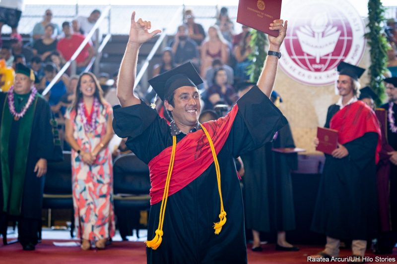 Male graduate flashing shaka to audience members as he is leaving dais with diploma.