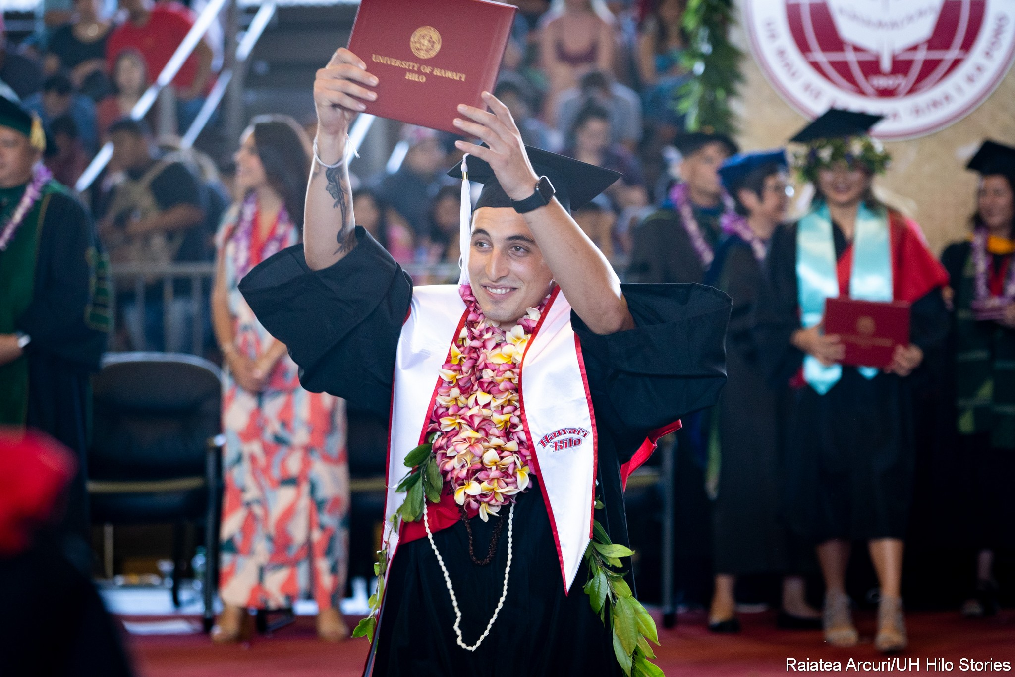 Male graduate with white shashshows diploma to audience members as he isleaving dais with diploma.