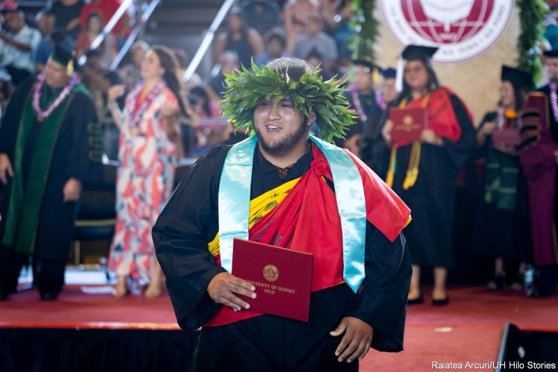 Male graduate with large green leaf haku lei and blue sash, red kihei, yellow kihei, leaving dais with diploma.