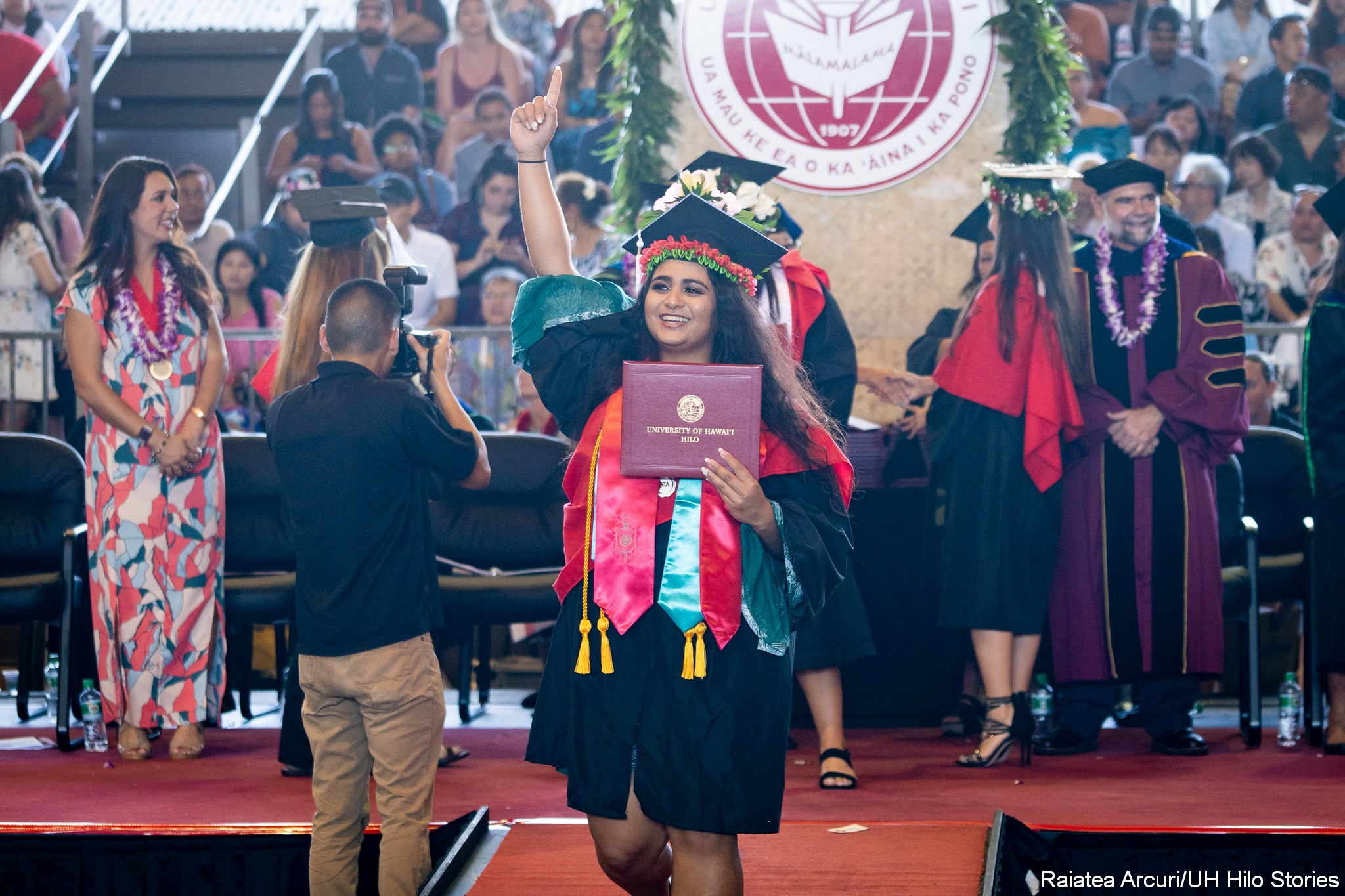 Female graduate signaling audience with a #1 from right hand, holds diploma in left hand as she is leaving dais.