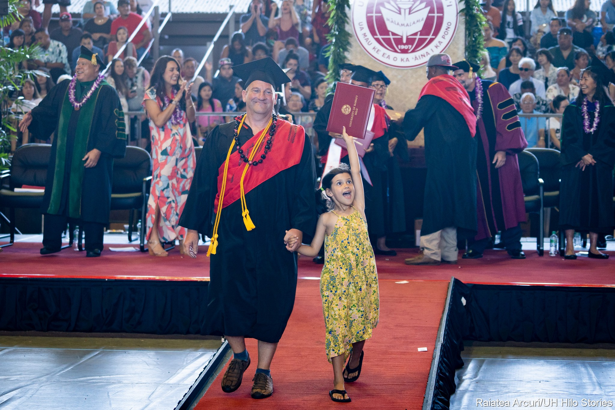 Female graduate leaving dais with young girl holding diploma high overhead.