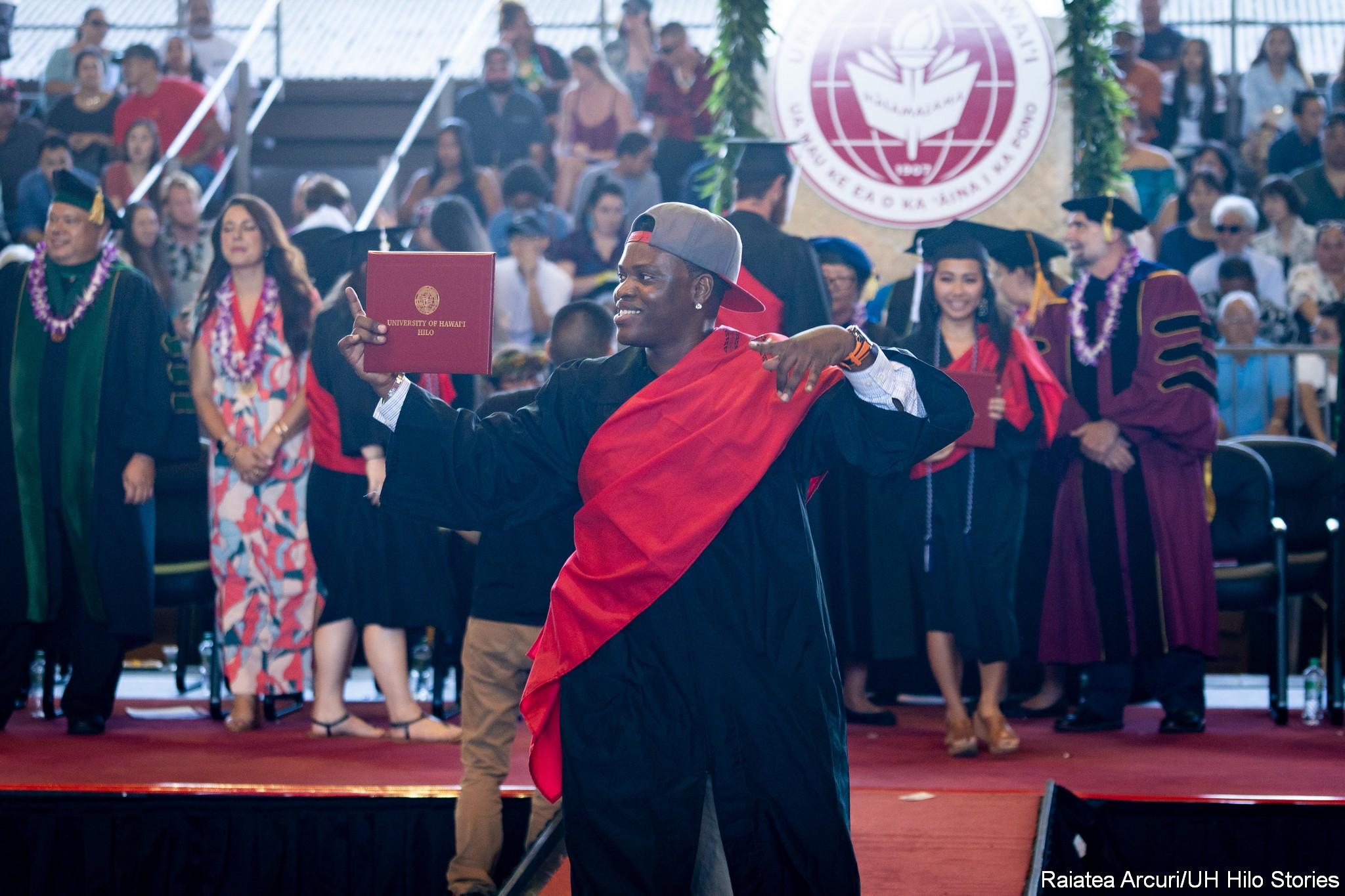 Male graduate with backward baseball cap leaving dais with diploma.
