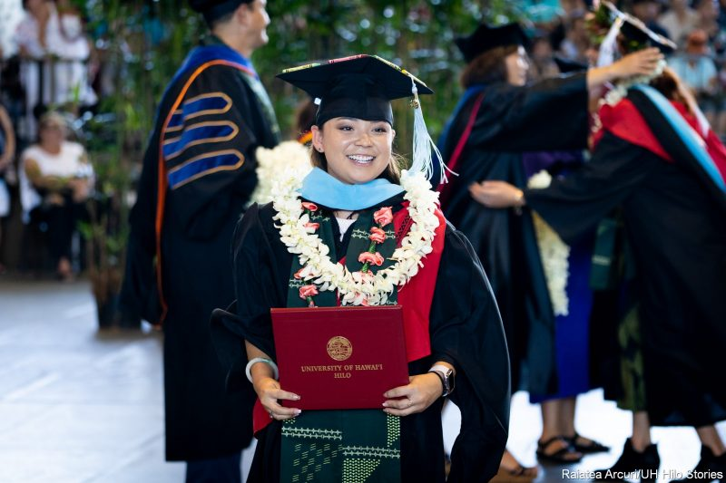 Female graduate with blue hood, white lei, holds up diploma.