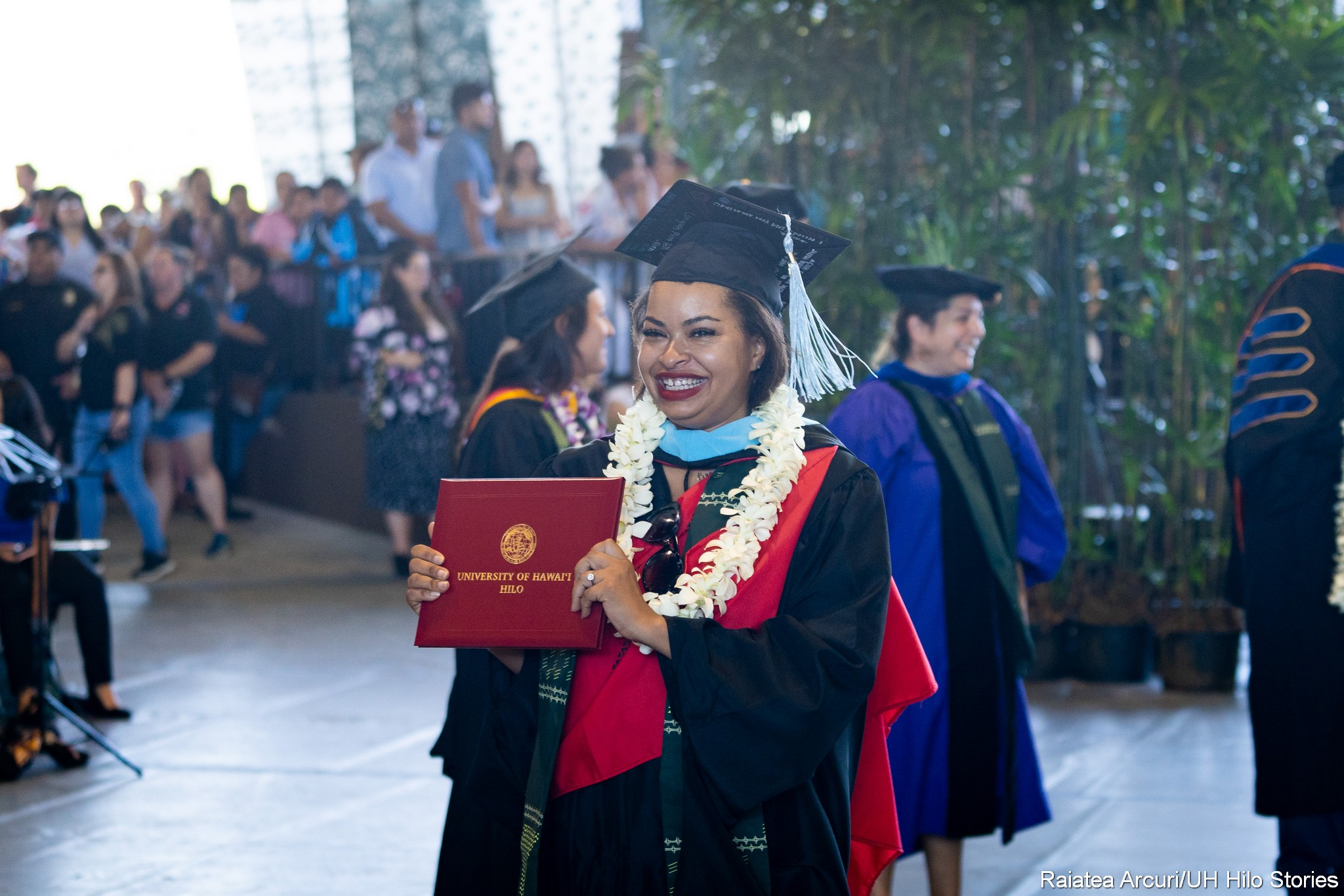 Female graduate, big smile, with blue hood, holds up diploma.