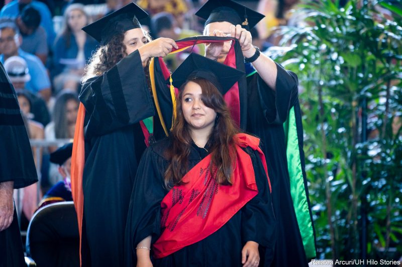 Female graduate looks to her right as she is in the process of being hooded, red hood.
