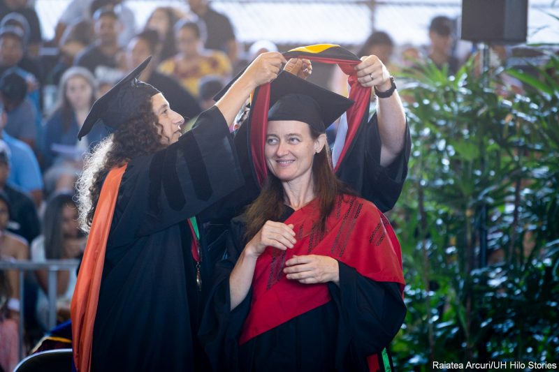 Female graduate lifts her hands up to chest while she is being hooded with red hood.