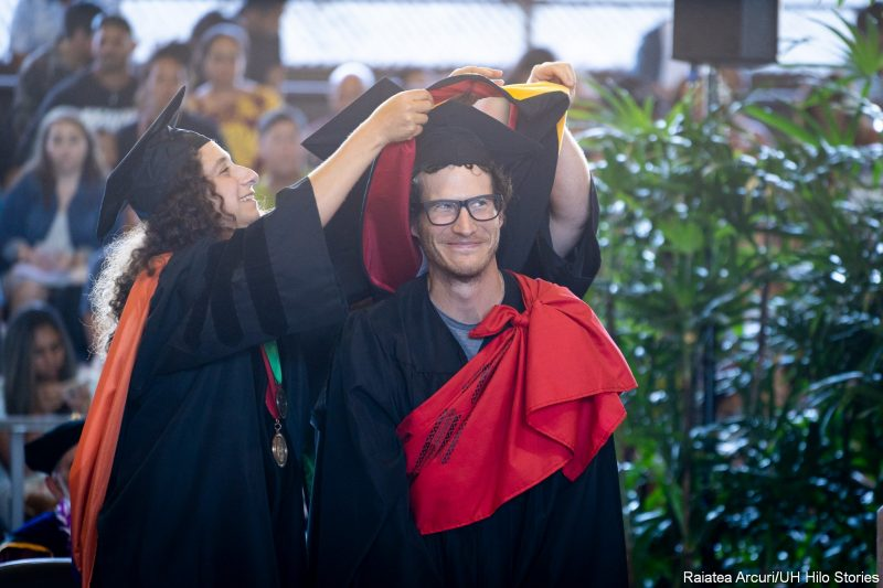 Male graduate stands still during his hooding ceremony.