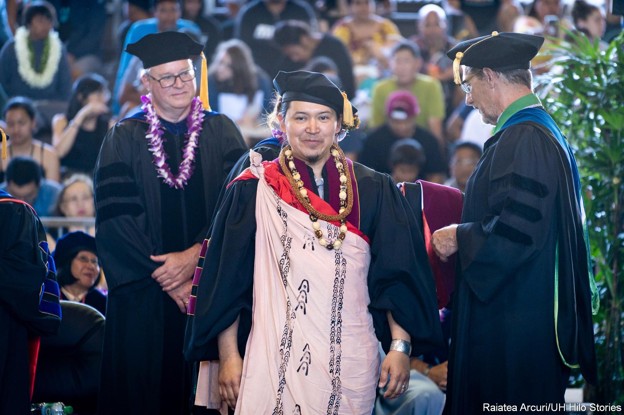 Officials adjust hood on a graduate.
