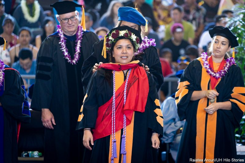Female graduate in red and white head lei on cap and wearing purple cord, receiving red hood.