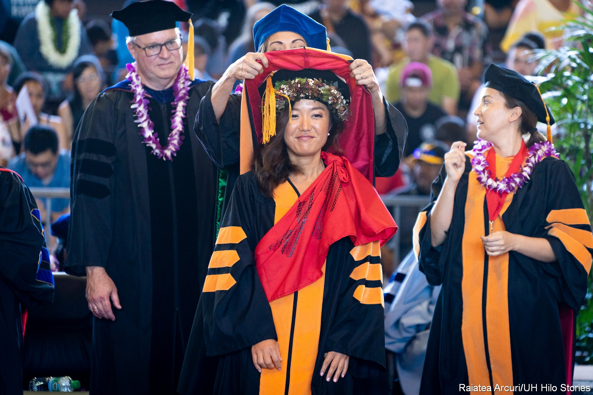 Red hood being placed on shoulders of female graduate.