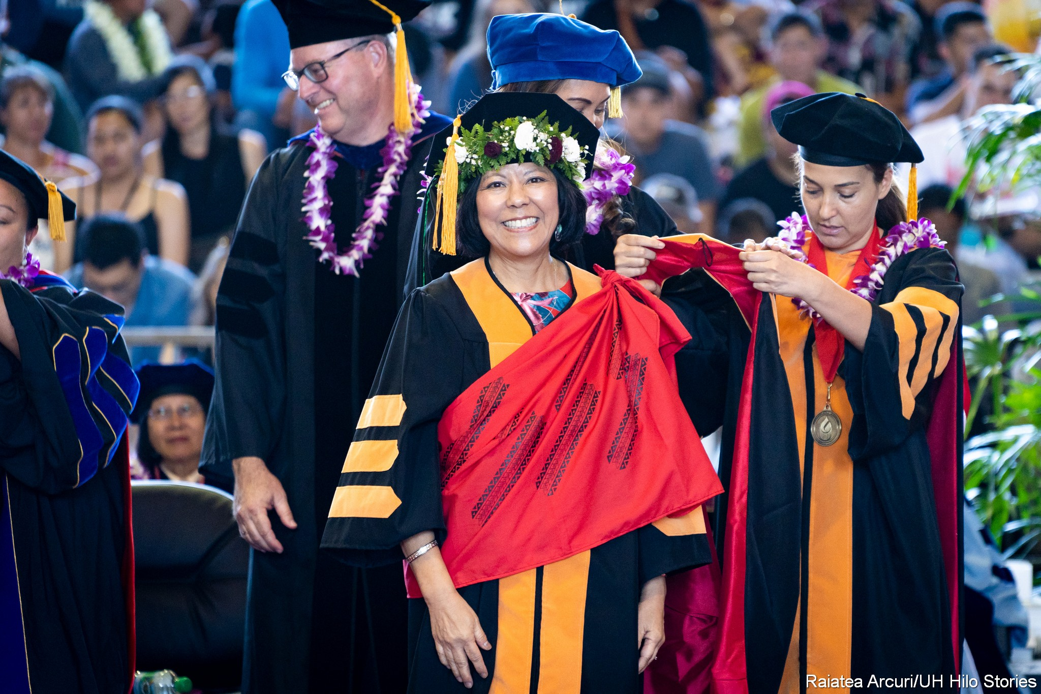 Smiling female graduate just about to receive hood. Official stands to right holding hood.