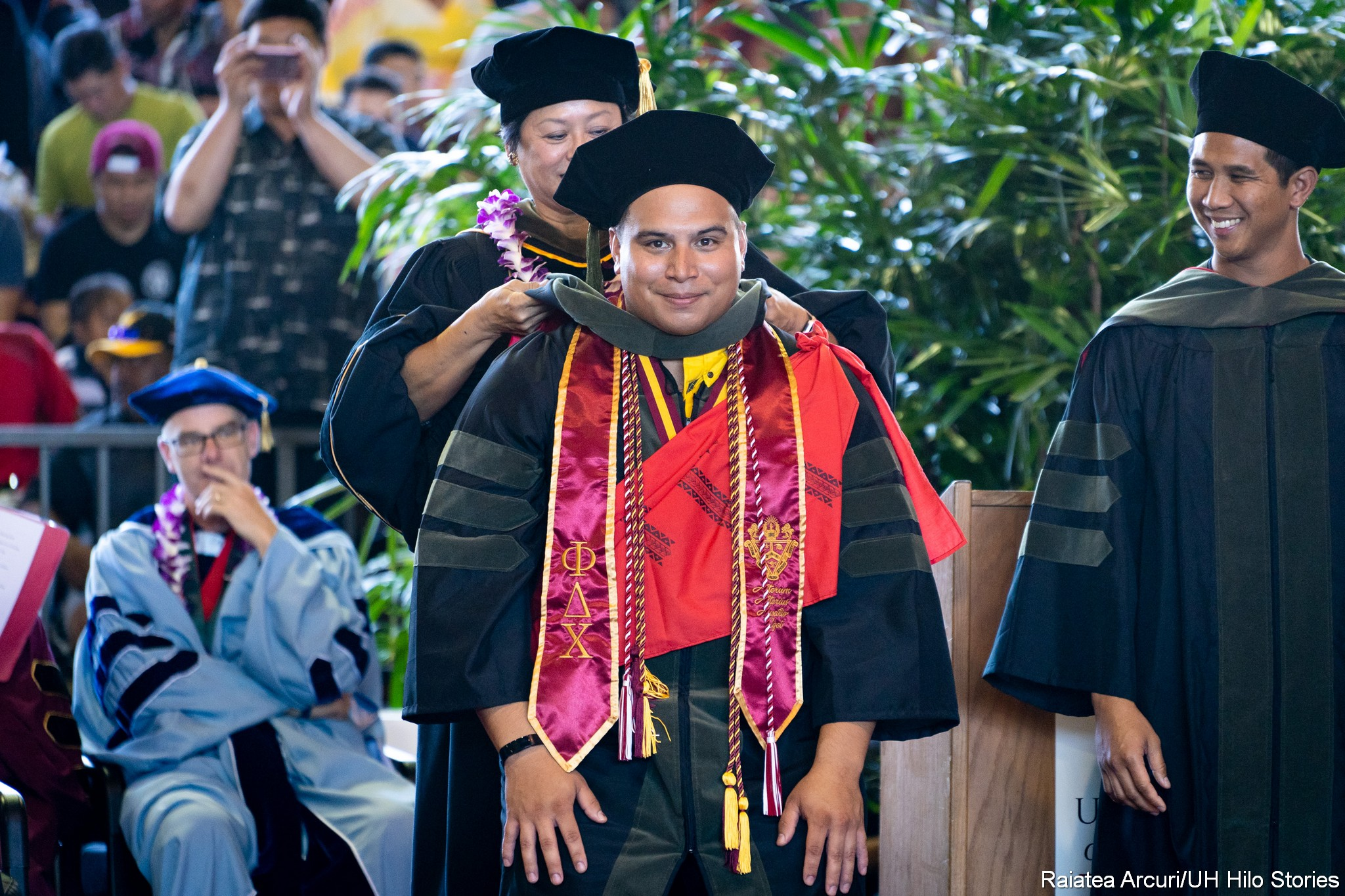 Male graduate looks straight into camera as he receives his hood.