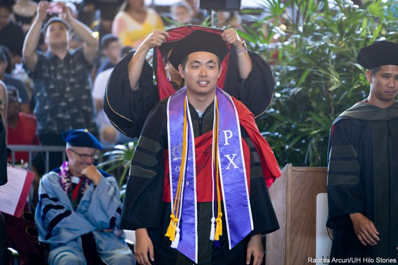 Official places hood on the shoulders of male graduate wearing purple sash and two cords.
