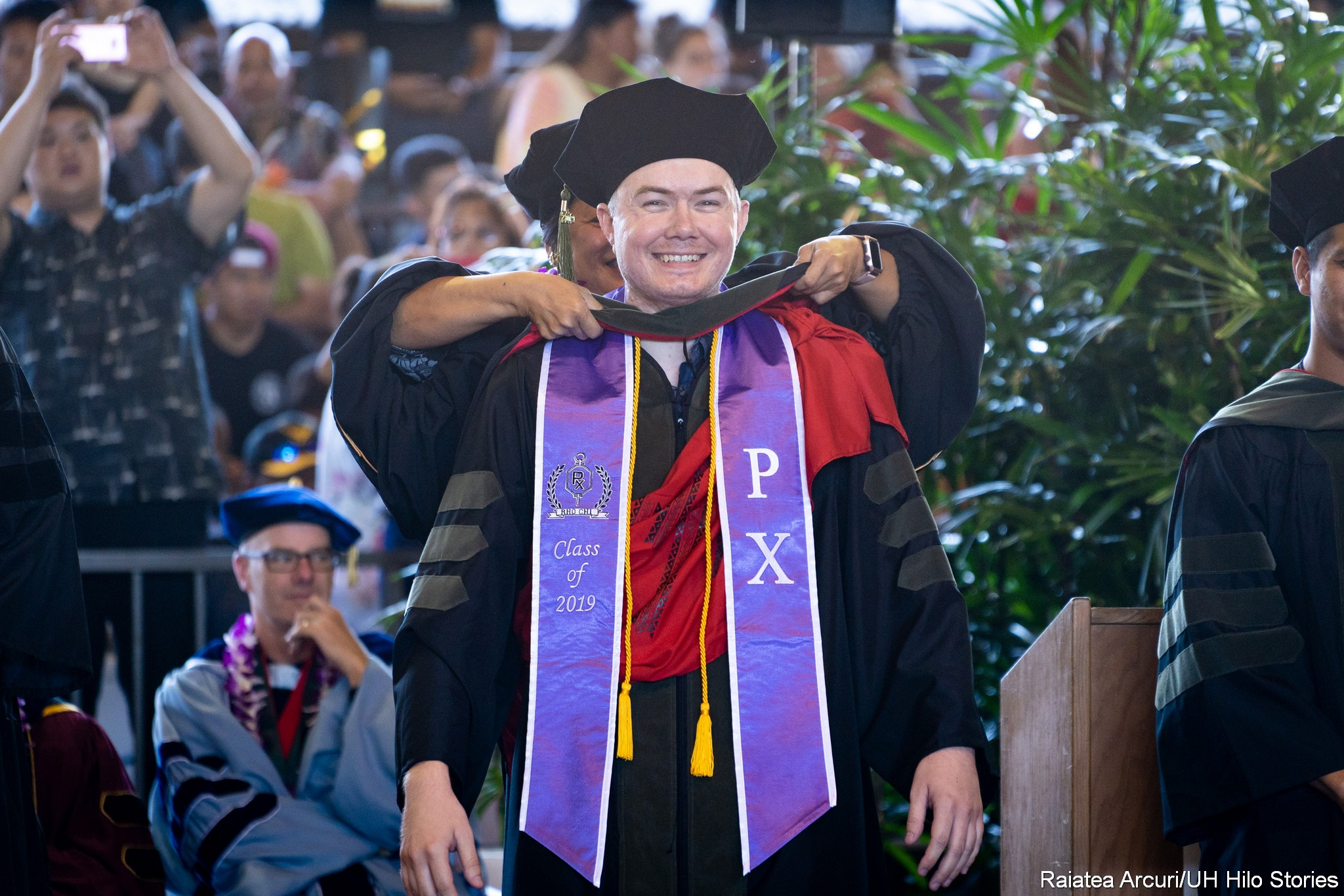 Male graduate with PX purple sash has hood placed on shoulders.