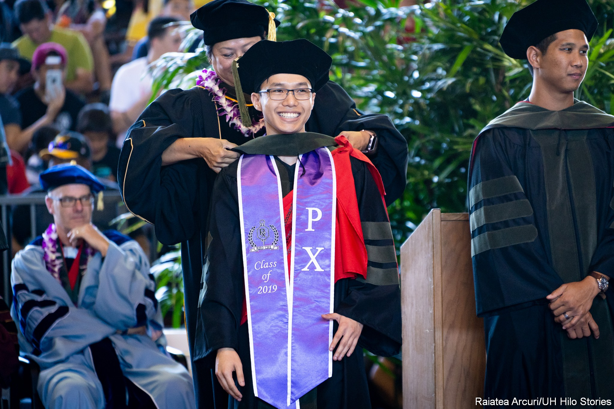 Male graduate with purple PX sash stands during his hooding.