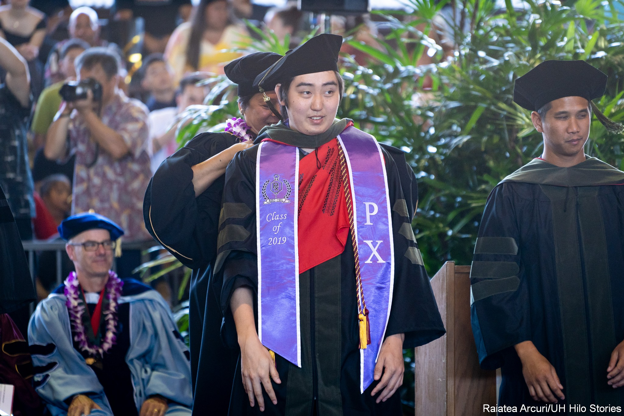 Male graduate looks to his left as dean places the hood on shoulders.