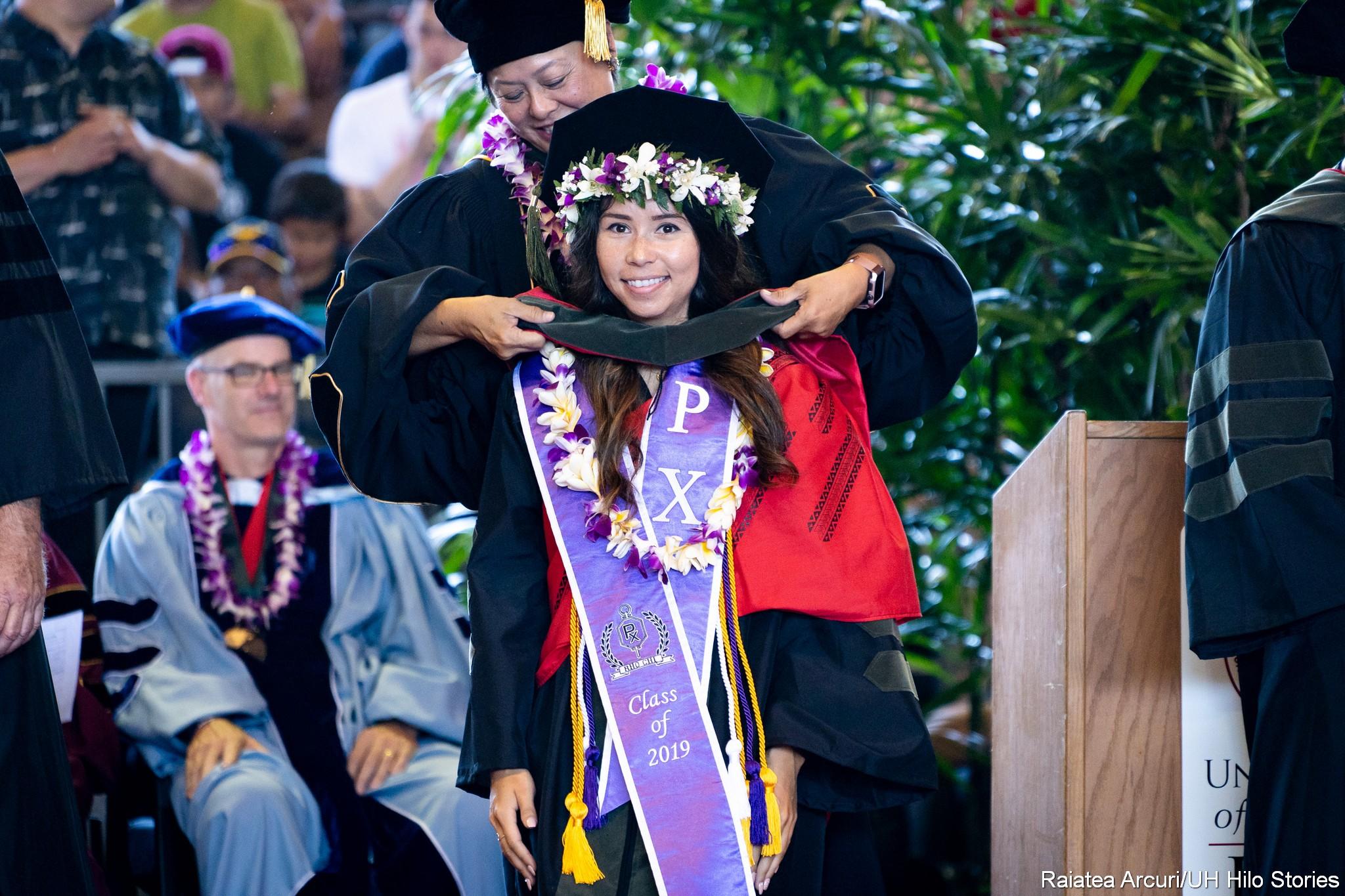 Female graduate wearing very wide purple sash receives her pharmacy hood.