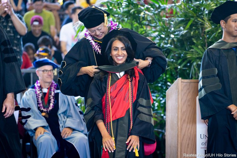 Smiling graduate stands while dean places hood on graduate's shoulders.