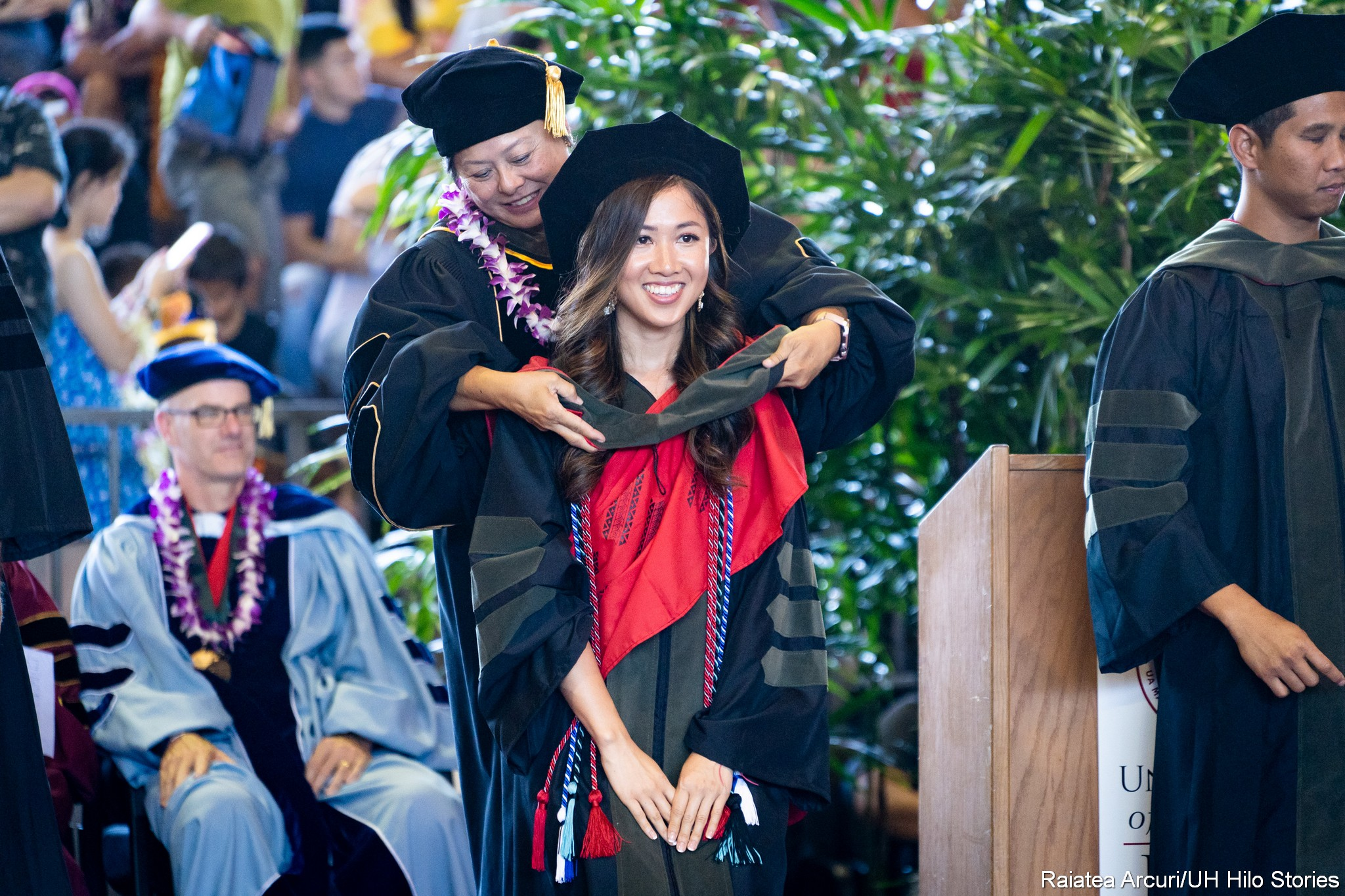 Smiling graduate stands while dean places hood on her shoulders.
