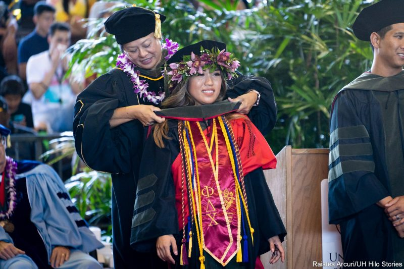 Female graduate with purple and green haku lei around her cap, with multiple cords, wide red sash, receives her hood.