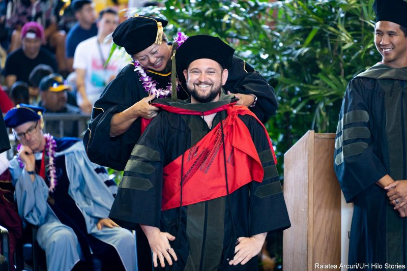 Smiling male graduate looks to side while dean places hood on his shoulders.