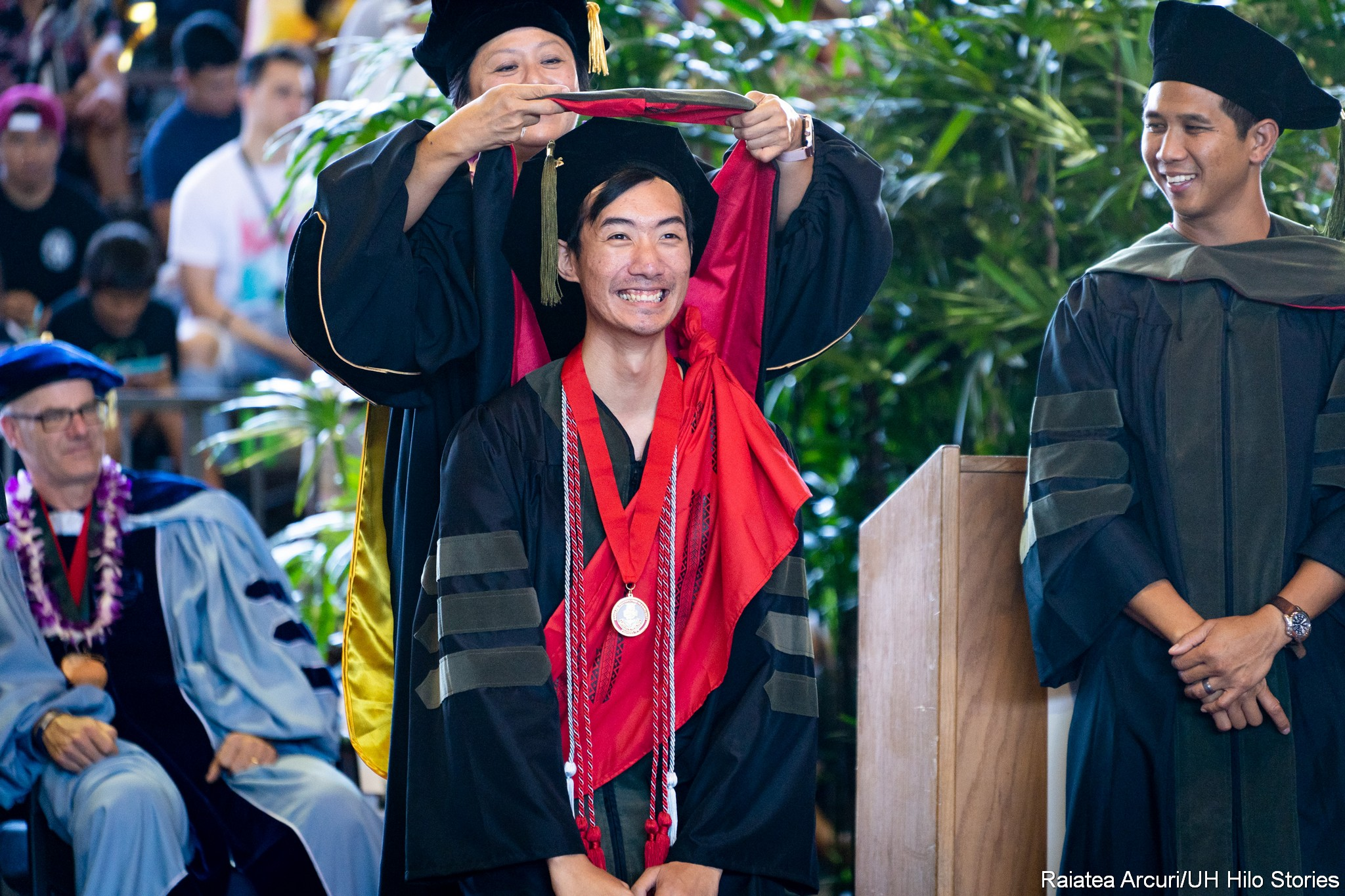 Male graduate stands with knees bent as dean places hood.