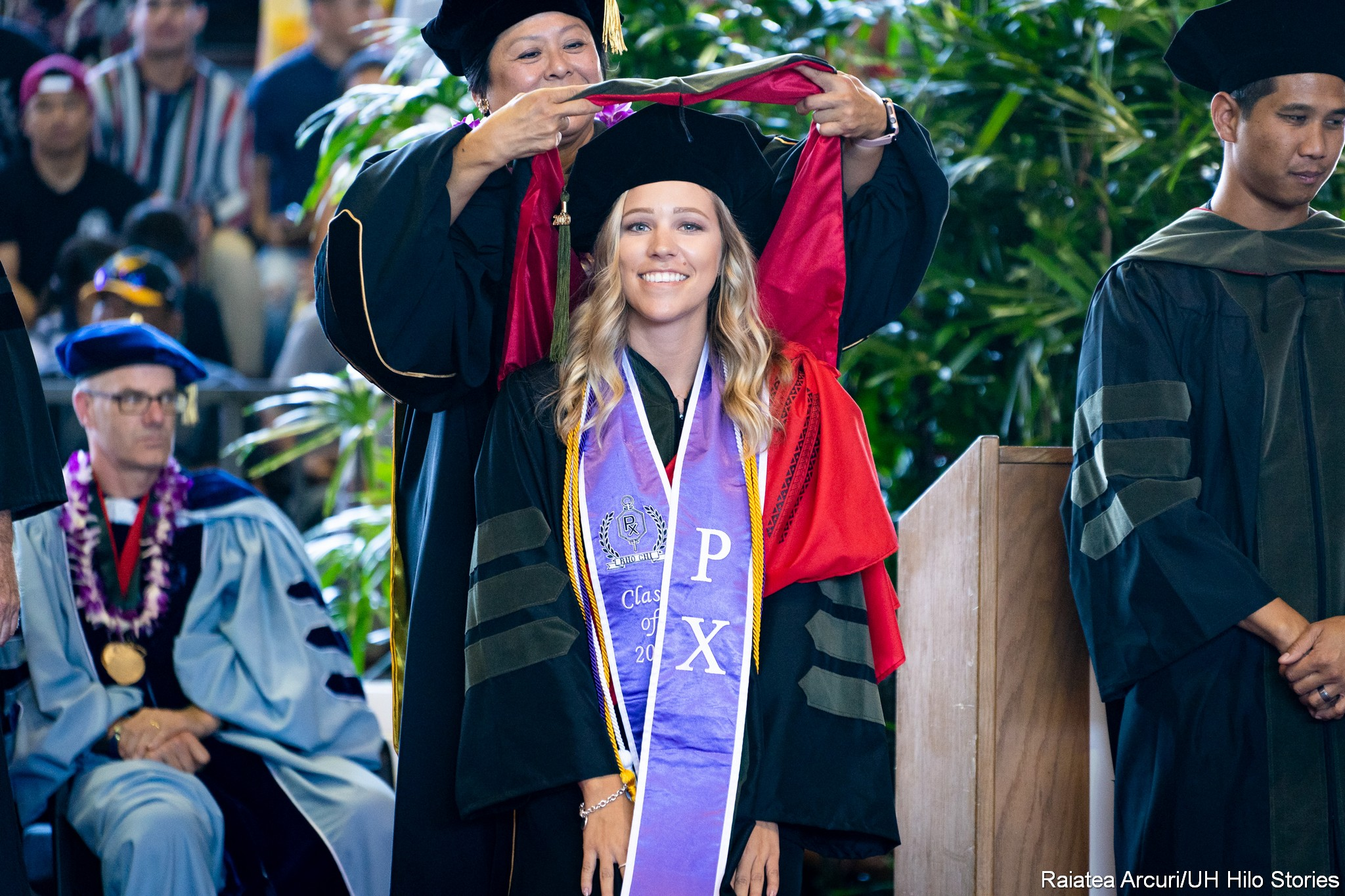 While standing behind student, dean raises hood up and over the head of a graduate.