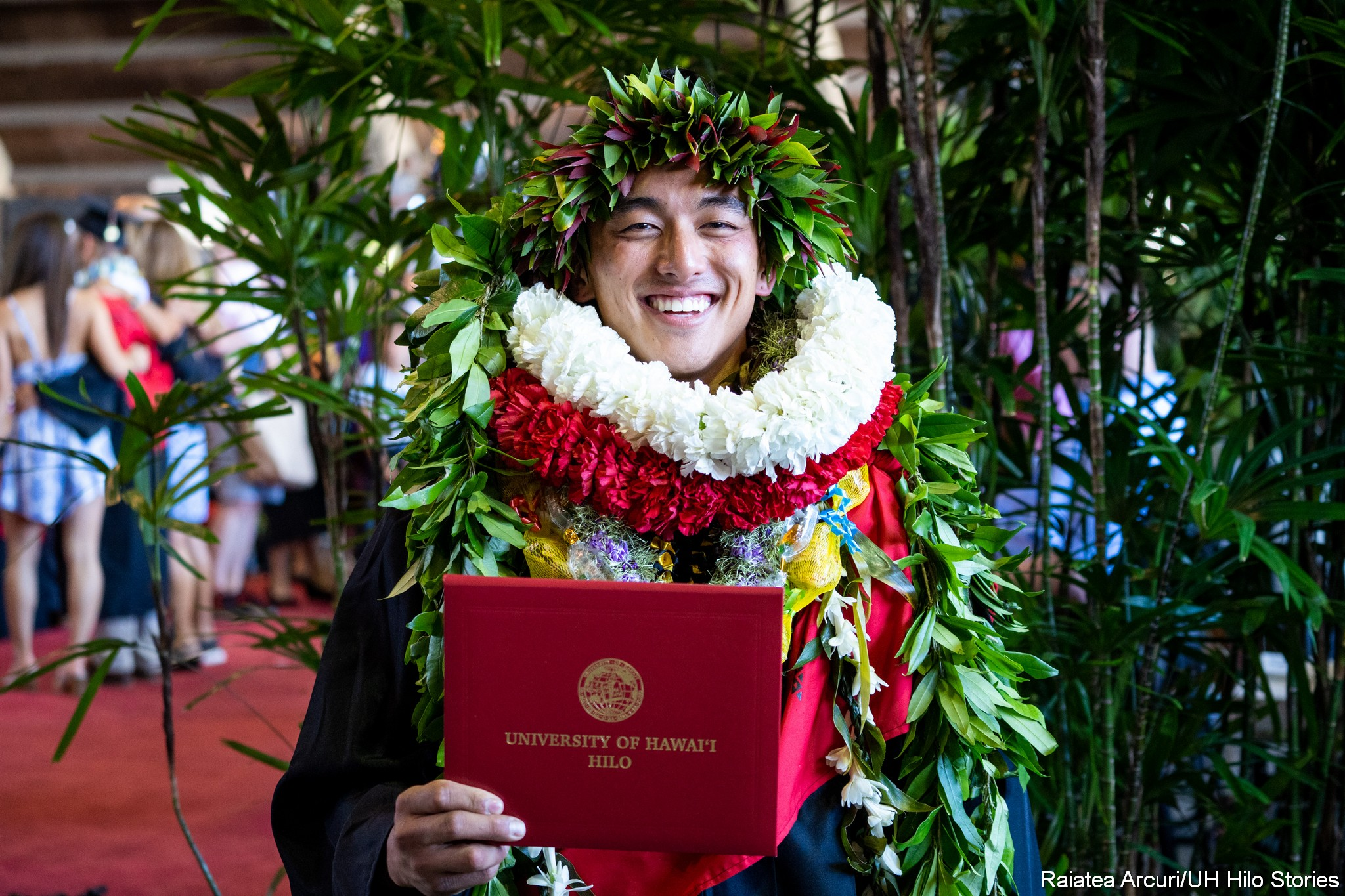After ceremonies, graduate stands decked with lei and holding diploma.