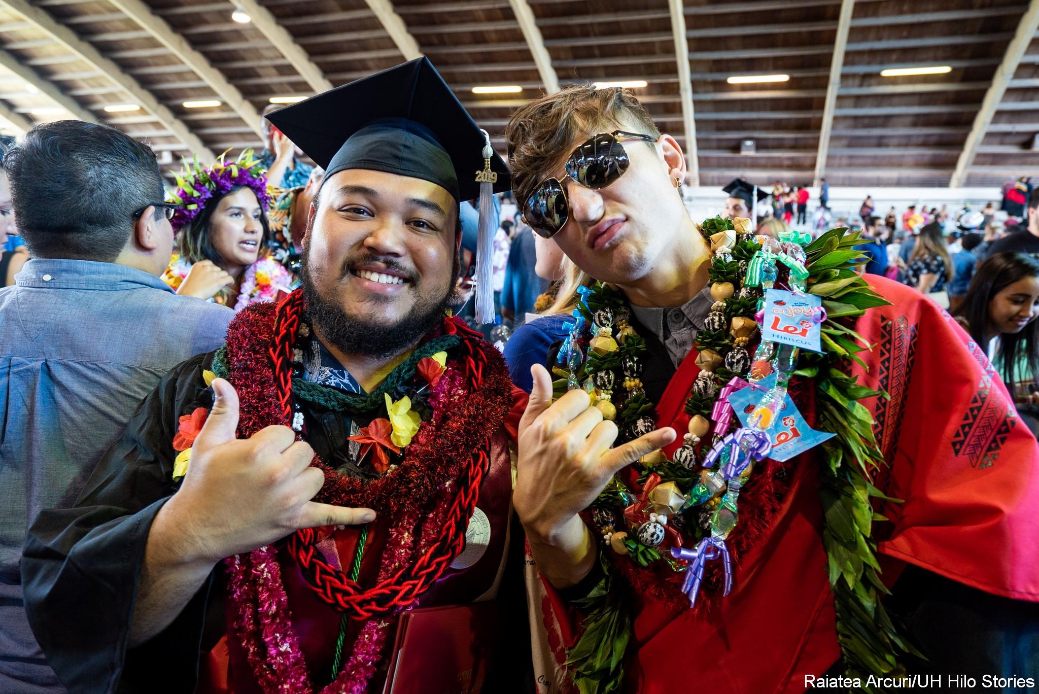 Two graduates with lei flash the shaka.