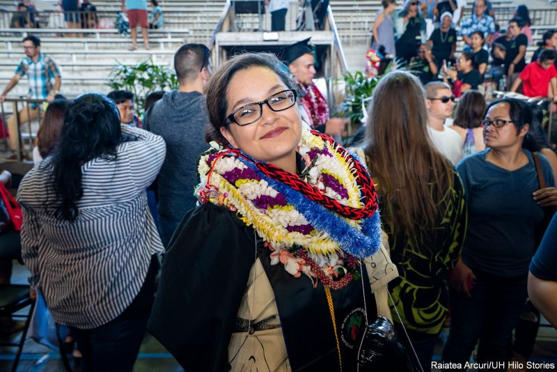 Female graduate with lei poses for photo..