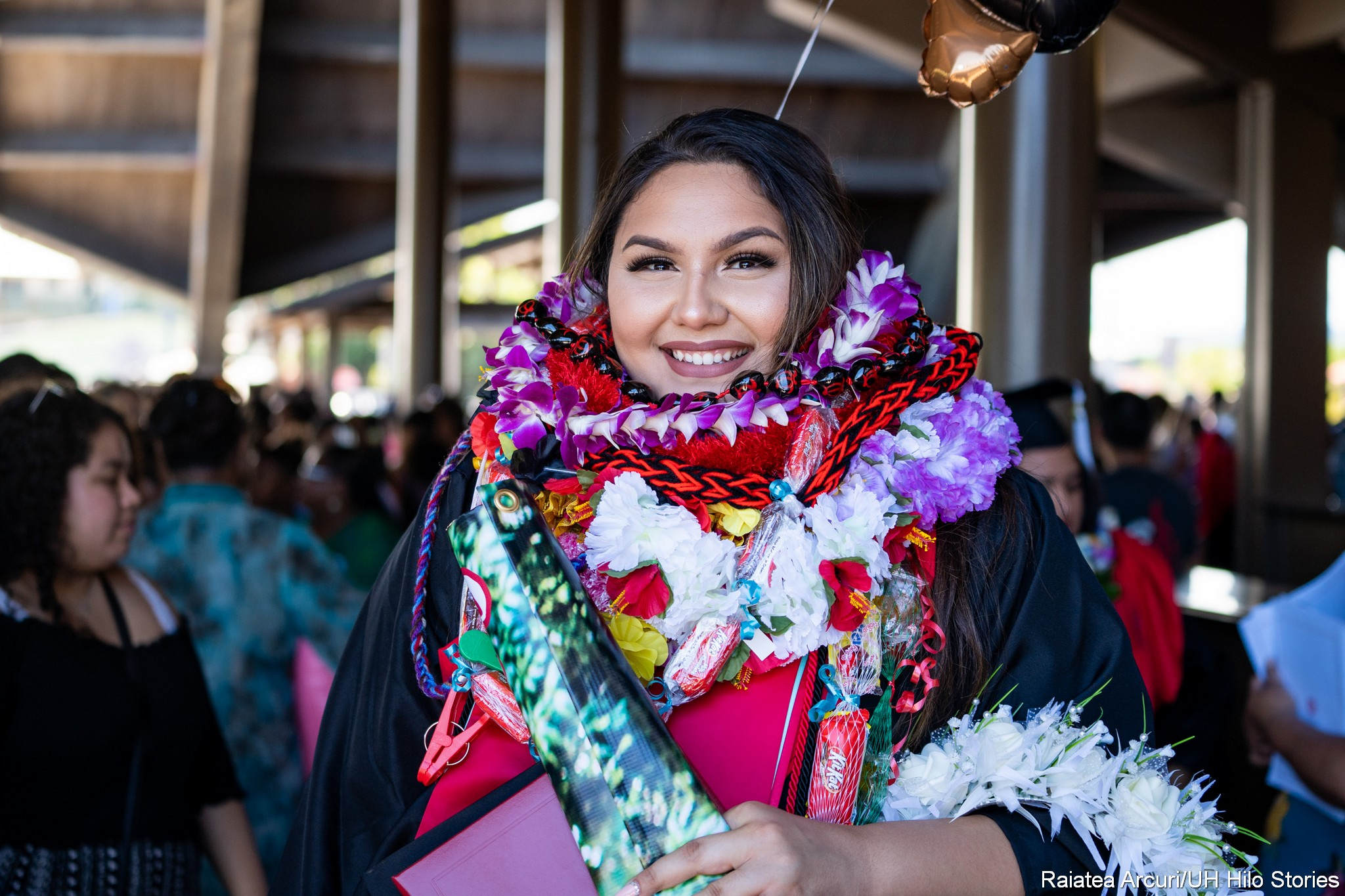Female graduate bedecked in lei poses for photo.