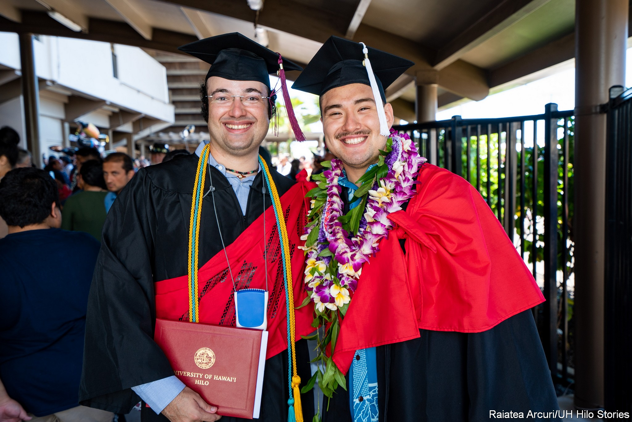 Two male graduates with big smiles pose for photo.