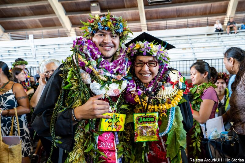 Two graduates with many lei pose for photo. One female, one male.