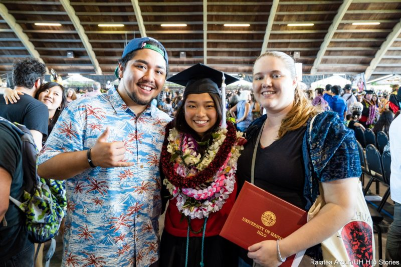 Graduate in many lei stands with parents.