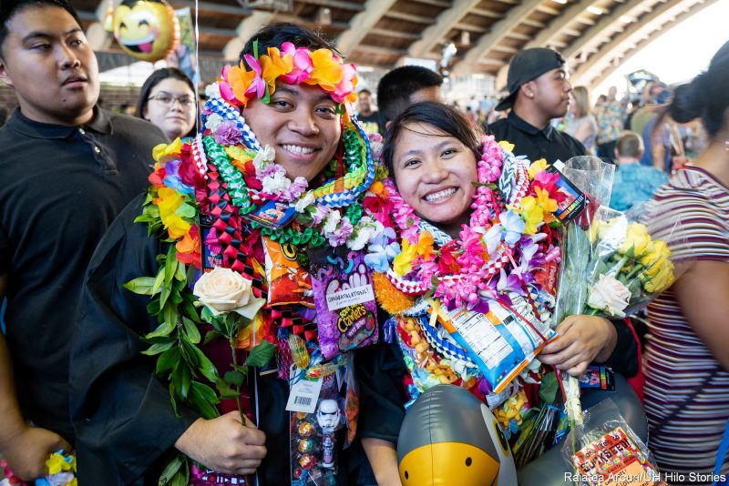 Two graduates with lei.