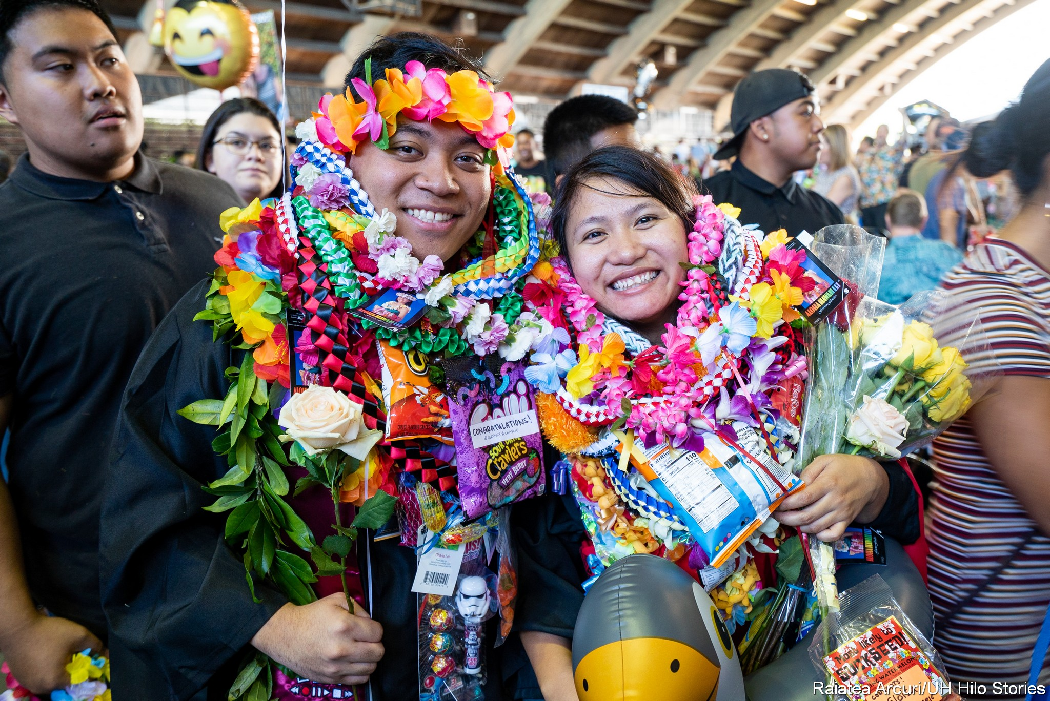 Two graduates with many lei and gifts.