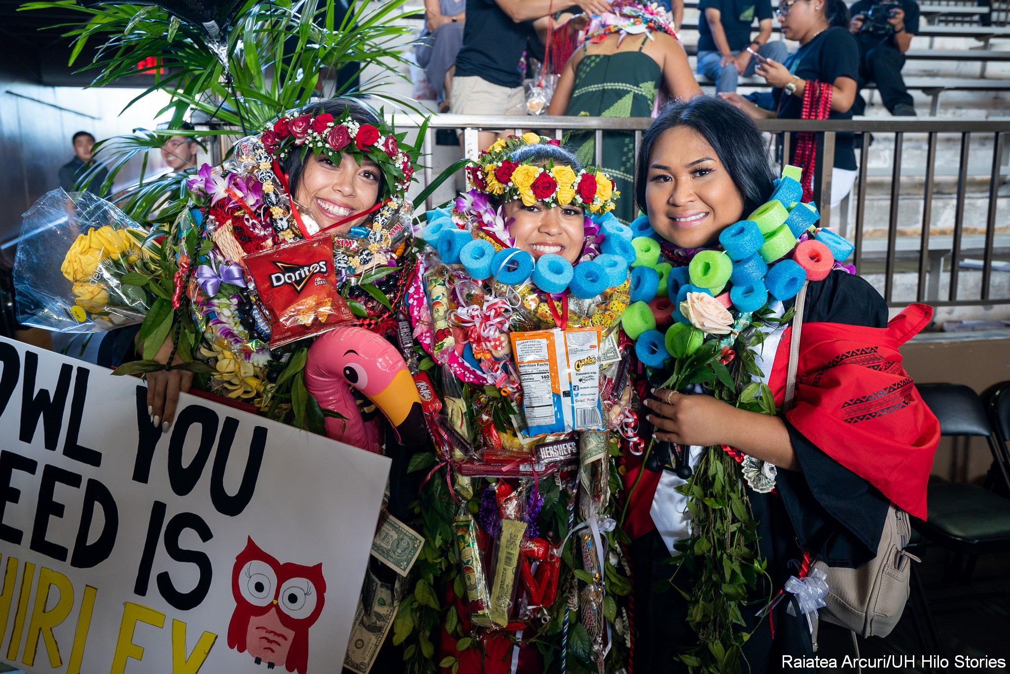 Three female graduates with many lei and gifts, big smiles.