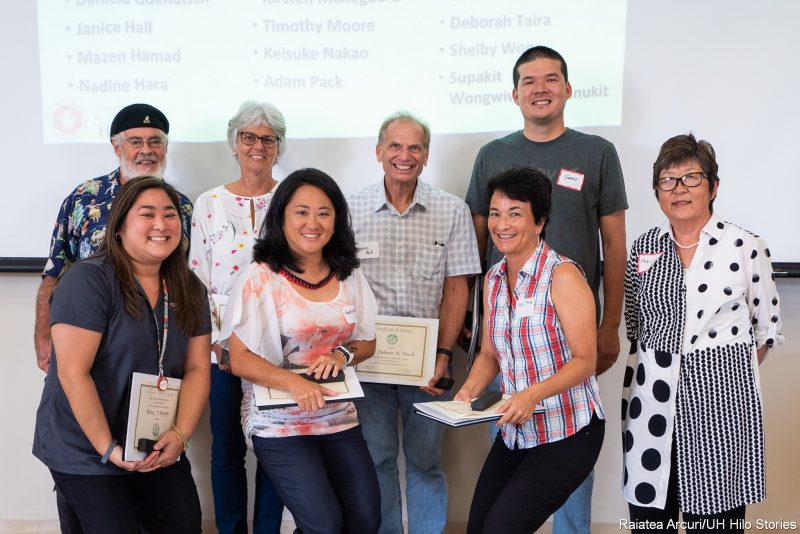 Group standing for photo, each person holding their certificate, Marcia Sakai at right of group.