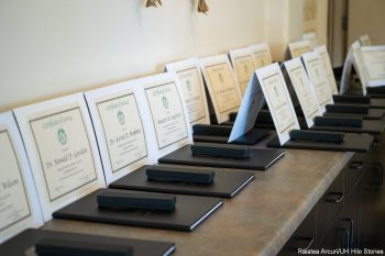 Certificates for years of service lined up on table before event.