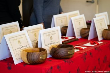 Koa bowls to be given to retirees are lined up on table covered with red cloth.