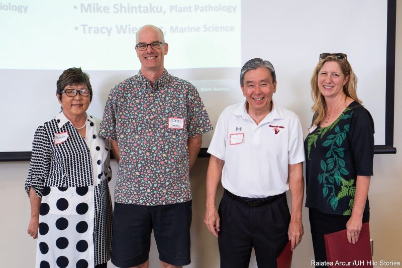 Marcia Sakai, Steven Lundblad, Randy Hirokawa, and Julie Mowrer stand in front of PowerPoint screen for photo.